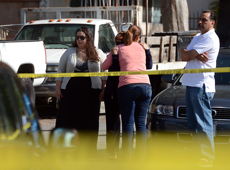 Photo - Family and friends gather outside the scene of a murder-suicide in Pomona, Calif., on Friday, May 9, 2014.  A 28-year-old man shot and killed three members of a Southern California family at the home where they all lived before turning the gun on himself, authorities said Friday. The four bodies were found late Thursday inside the single-story house in a residential area of Pomona, police Lt. Michael Keltner said at a morning news conference.  A woman in her 50s and her 24-year-old daughter and 17-year-old son were killed in their respective bedrooms, he said. (AP Photo/The Inland Valley Daily Bulletin, Jennifer Cappuccio Maher)  MANDATORY CREDIT