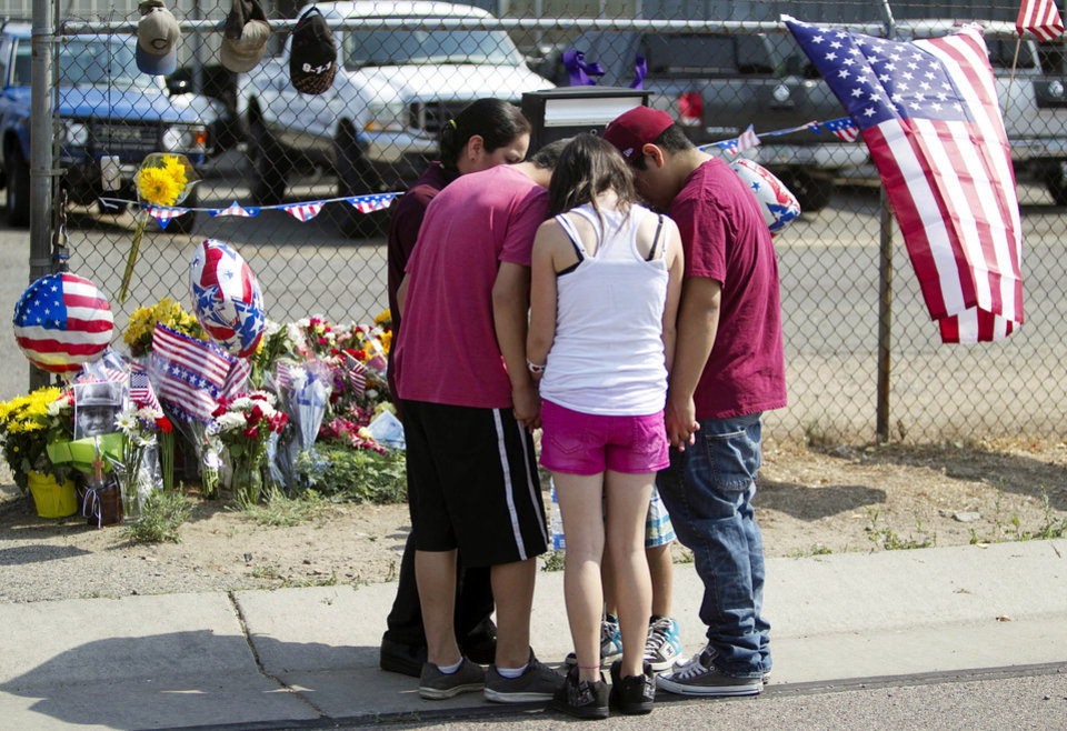 Photo - The Bragg family gathers near a makeshift memorial at the fire station Monday, July 1, 2013, in Prescott, Ariz., where an elite team of firefighters was based. Nineteen of the 20 members of the team were killed Sunday when a wildfire suddenly swept toward them in Yarnell, Ariz. (AP Photo/The Arizona Republic, Patrick Breen)