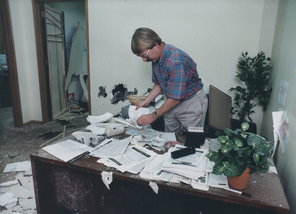 Photo - 20th ANNIVERSARY OF HB-1017.  Dan Brown with the Oklahoma Taxpayers Union, sorts through papers on a desk in the organization's front office , which sustained the heaviest damage from an explosion.   Photo taken Sep. 30, 1991. by Jim Beckel, The Oklahoman.