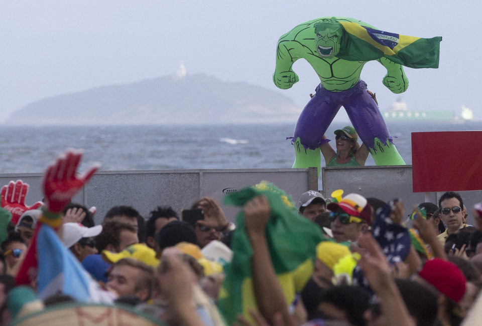 Photo - A woman holds up an inflatable Hulk doll, a reference to Brazil's soccer player Hulk, at the FIFA Fan fest area where fans gather to watch the World Cup soccer game between Brazil and Croatia on Copacabana beach in Rio de Janeiro, Brazil, Thursday, June 12, 2014. (AP Photo/Silvia Izquierdo)