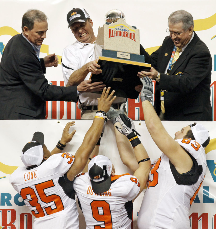 Photo - OSU head coach Mike Gundy hands the trophy to Mathies Long (35), Bo Bowling (9) and Jordan Taormina (63) after the Valero Alamo Bowl college football game between the Oklahoma State University Cowboys (OSU) and the University of Arizona Wildcats at the Alamodome in San Antonio, Texas, Wednesday, December 29, 2010. OSU won, 36-10. Photo by Nate Billings, The Oklahoman