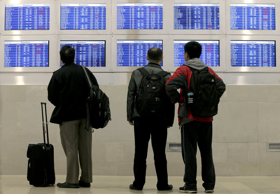 Travelers look at a departure screen Monday, Oct. 29, 2012, in Detroit. The parent of United Airlines reported a $620 million quarterly loss on Thursday as travelers stayed away following its problems earlier in the year with absorbing Continental. Superstorm Sandy cut $85 million from its results in 2012's final quarter. (AP Photo/Charlie Riedel)