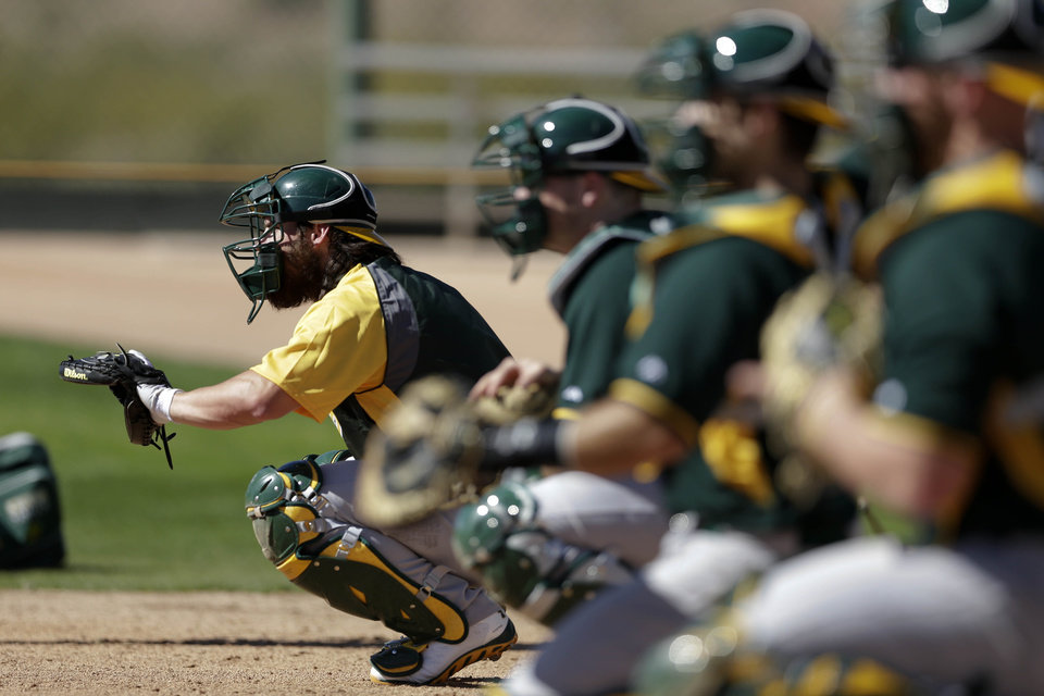 Photo - Oakland Athletics catcher Derek Norris, left, waits for a pitch in a line of catcher during spring training baseball practice Saturday, Feb. 15, 2014, in Scottsdale, Ariz.  (AP Photo/Gregory Bull)