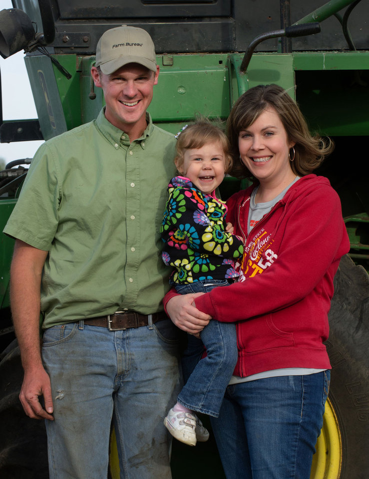 "This September 2012 photo provided by the Iowa Farm Bureau shows farmer Randy Dreher, his wife, Crystal, and their 2-year-old daughter, Kaytlin, north of Audubon, Iowa. Dreher says he and his wife have saved more in recent years, but being prudent and conservative has its limits. ""You can be responsible and be making progress in your own little world, but there are outside factors you can't control,"" he says. ""You prepare for the worst, but you can only do so much."" (AP Photo/Iowa Farm Bureau, Gary Fandel)"