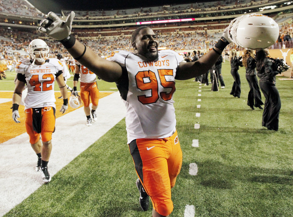 Photo - OSU's Chris Donaldson (95) acknowledges the Cowboy fans after the college football game between the Oklahoma State University Cowboys (OSU) and the University of Texas Longhorns (UT) at Darrell K Royal-Texas Memorial Stadium in Austin, Texas, Saturday, November 13, 2010. Justin Gent (42) is in the background. OSU won, 33-16. Photo by Nate Billings, The Oklahoman
