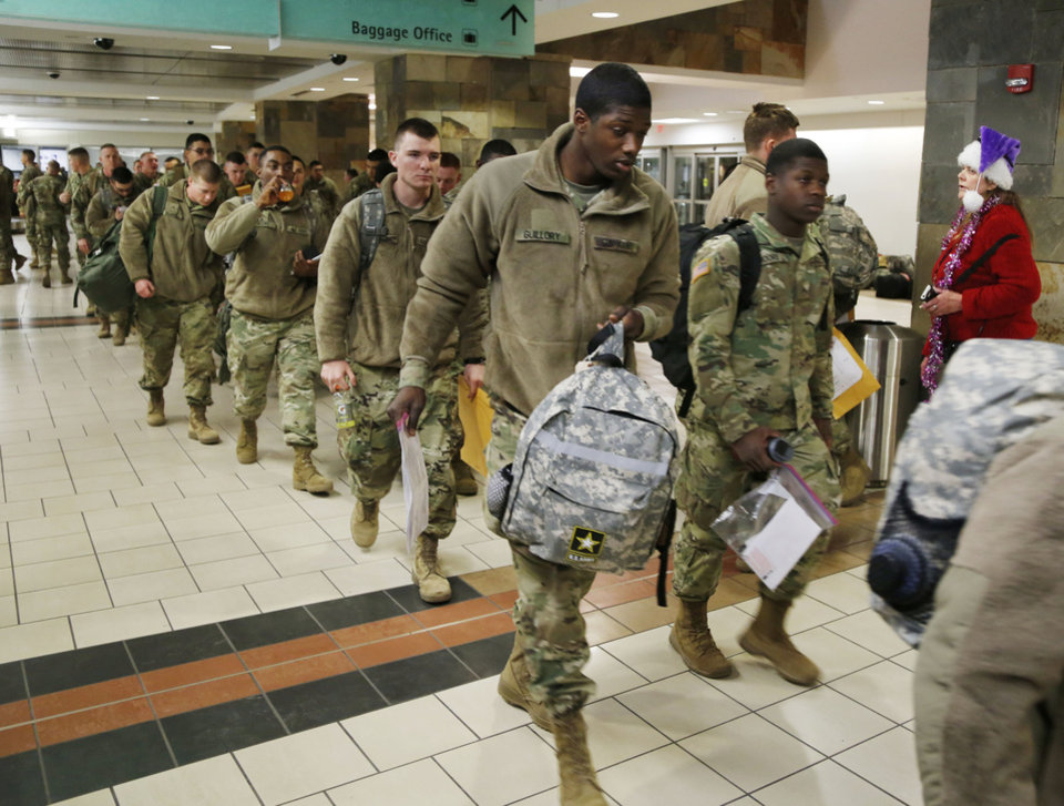Photo - Soldiers from Ft. Sill head toward their gate at Will Rogers World Airport in Oklahoma City, Okla. on their way home for Christmas, Monday, Dec. 19, 2016.  Photo by Paul Hellstern, The Oklahoman