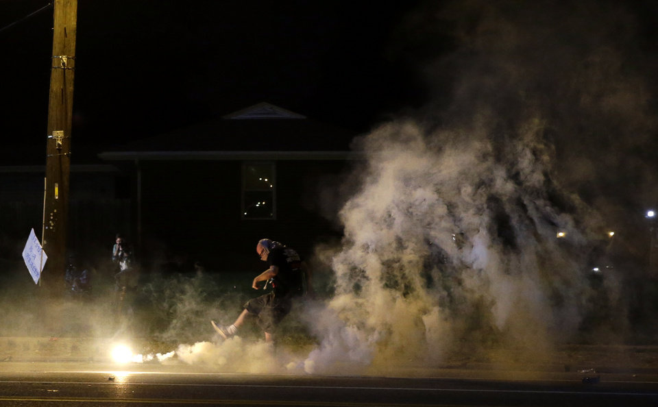 Photo - A protester kicks a smoke grenade deployed by police back in the direction of police, Wednesday, Aug. 13, 2014, in Ferguson, Mo. Protests in the St. Louis suburb rocked by racial unrest since a white police officer shot an unarmed black teenager to death turned violent Wednesday night, with people lobbing Molotov cocktails at police who responded with smoke bombs and tear gas to disperse the crowd. (AP Photo/Jeff Roberson)
