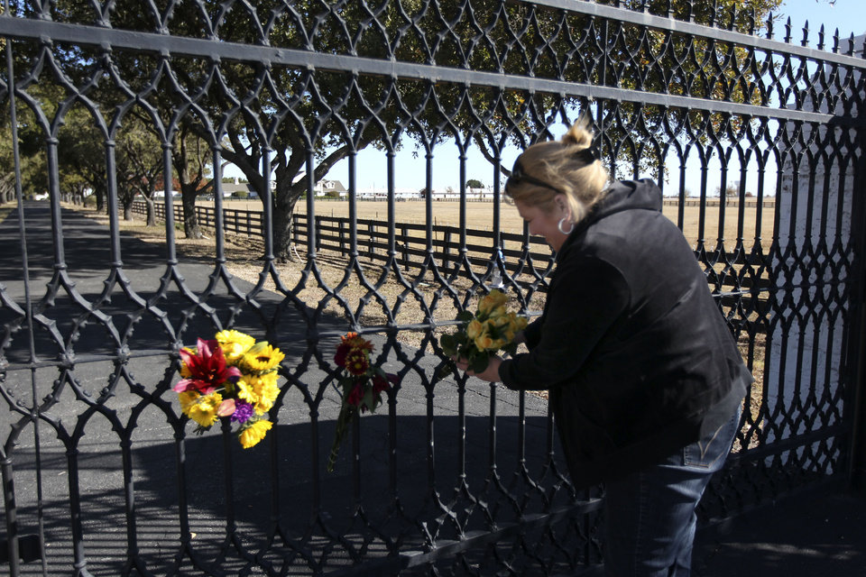Photo -   Kelli Pearson of Rowlett, attaches a bouquet of yellow roses to the front gate of Southfork Ranch, setting for TV show