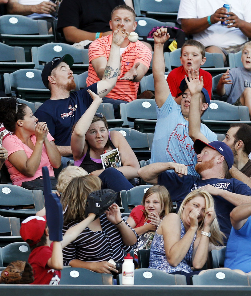 Photo - Fans try to catch a foul ball during a minor league baseball game between the Oklahoma City RedHawks and the Las Vegas 51s at the Chickasaw Bricktown Ballpark in Oklahoma City, Friday, June 13, 2014. Photo by Nate Billings, The Oklahoman