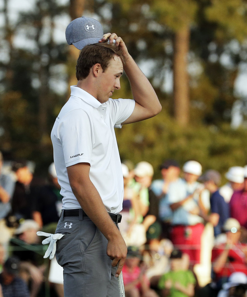Photo - Jordan Spieth takes his cap off after putting on the 18th hole during the second round of the Masters golf tournament Friday, April 11, 2014, in Augusta, Ga. (AP Photo/Charlie Riedel)