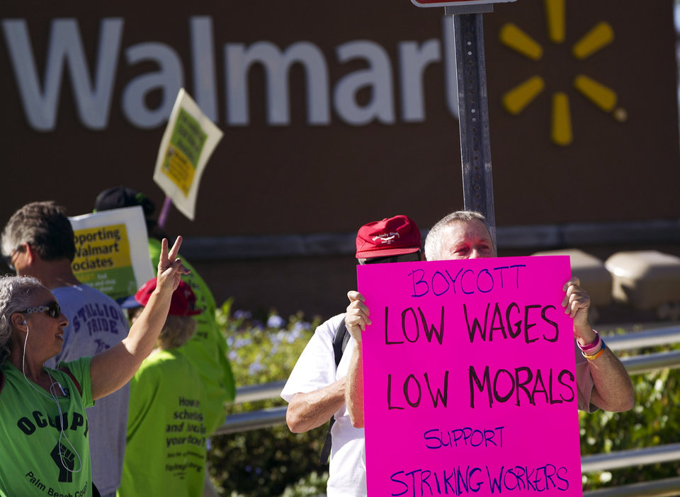 Photo -   Demonstrators protest Wal-Mart in Boynton Beach, Fla., Friday, Nov 23, 2012. Wal-Mart employees and union supporters are taking part in today's nationwide demonstration for better pay and benefits A union-backed group called OUR Walmart, which includes former and current workers, was staging the demonstrations and walkouts at hundreds of stores on Black Friday, the day when retailers traditionally turn a profit for the year. (AP Photo/J Pat Carter)
