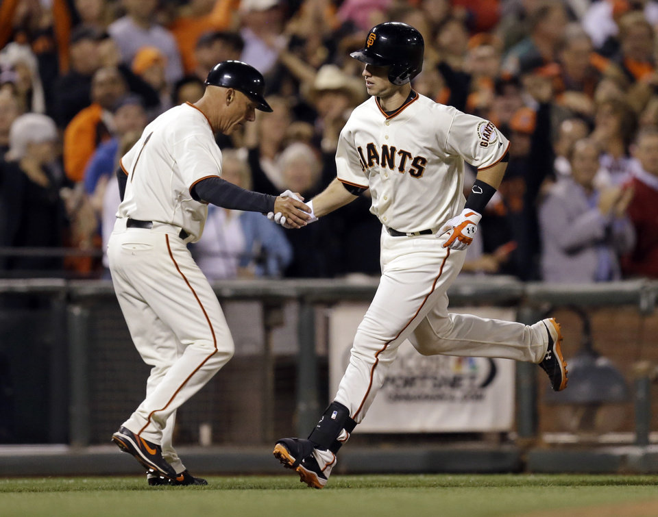 Photo - San Francisco Giants' Buster Posey, right, is congratulated by third base coach Tim Flannery after Posey hit a home run off Colorado Rockies' Brooks Brown in the eighth inning of a baseball game Tuesday, Aug. 26, 2014, in San Francisco. (AP Photo/Ben Margot)