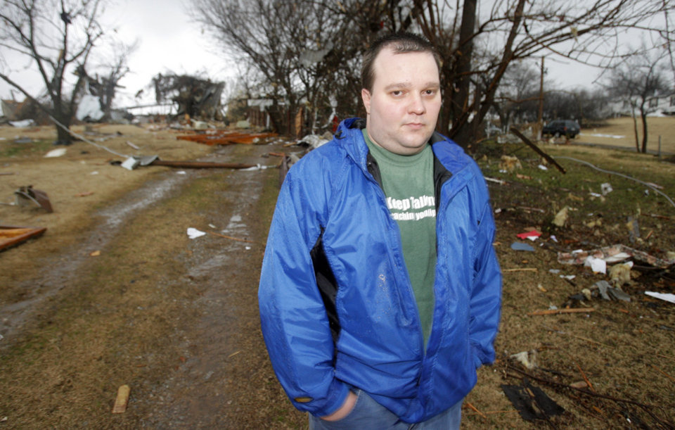 Photo - John Burdick looks over his neighbor's tornado-damaged home north of Waterloo on Broadway, Tuesday , February 10, 2009.  By David McDaniel, The Oklahoman.
