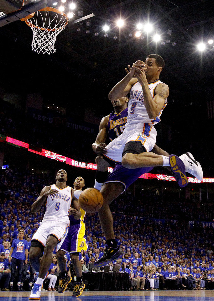 Photo - Oklahoma City's Thabo Sefolosha (2) falls after being fouled by Los Angeles' Metta World Peace (15) during Game 5 in the second round of the NBA playoffs between the Oklahoma City Thunder and the L.A. Lakers at Chesapeake Energy Arena in Oklahoma City, Monday, May 21, 2012. Photo by Sarah Phipps, The Oklahoman
