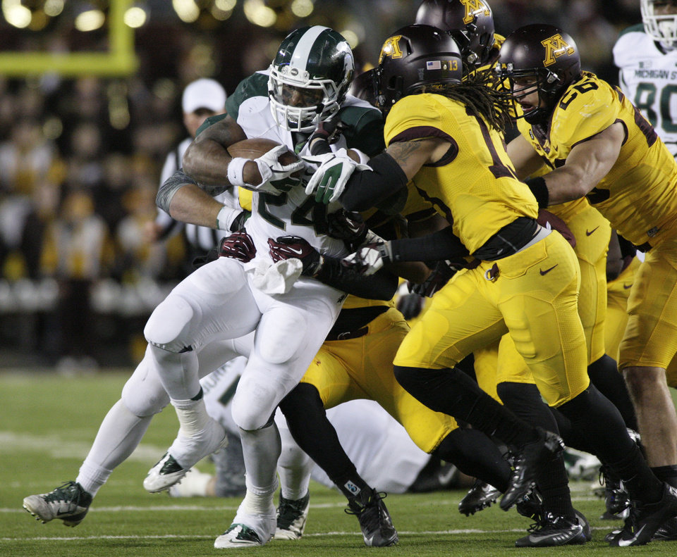 Photo -   Michigan State running back Le'Veon Bell (24) is gang-tackled during the second half of an NCAA college football game against Minnesota, Saturday, Nov. 24, 2012, in Minneapolis. Michigan State won 26-10. (AP Photo/Paul Battaglia)