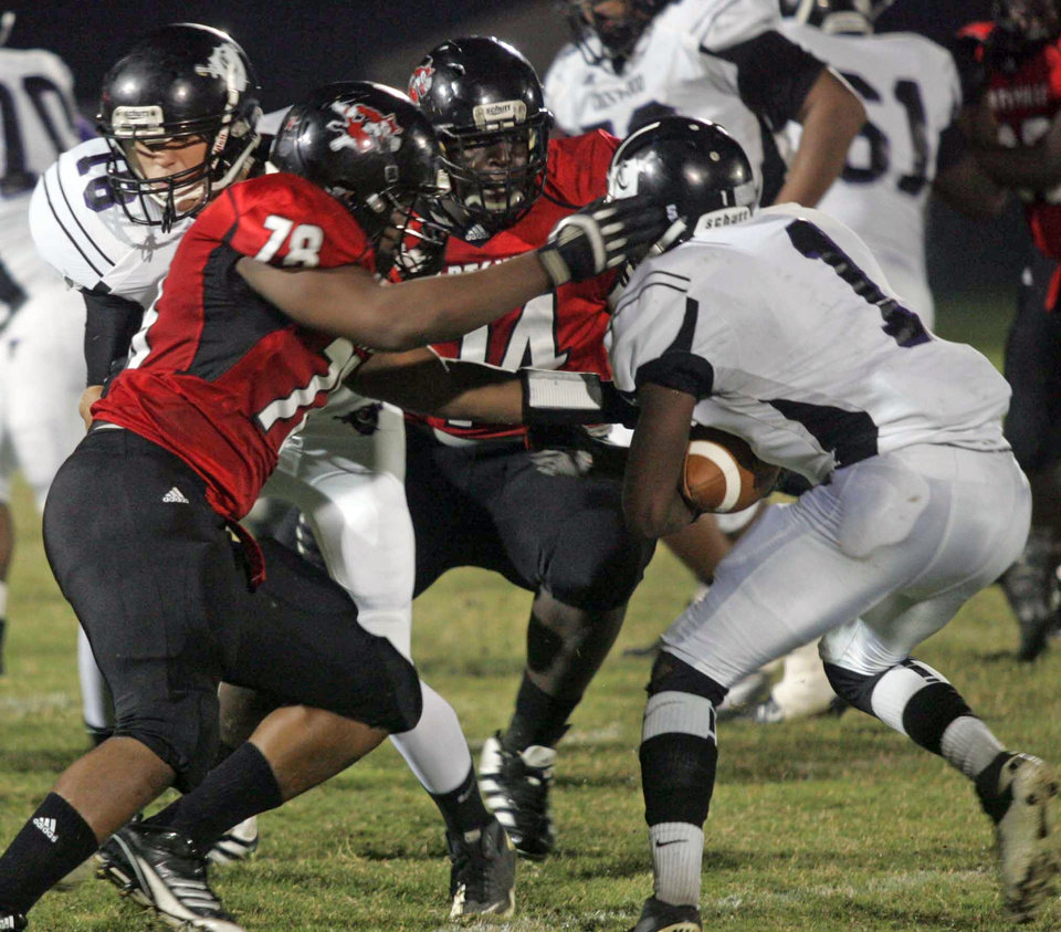 Photo -   Hartsville defenders Dwayne McDaniel (78) and Ronald Rouse (74) tackle Crestwood running back Rakeen Benjamin during the first quarter of Friday's game in Hartsville. Rouse collapsed during the second quarter of the game and later died at a local hospital. The game was suspended at halftime. (AP Photo/Bob Sloan, Florence Morning News)