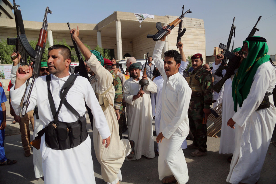 Photo - Iraqi Shiite tribal fighters raise their weapons and chant slogans against the al-Qaida inspired Islamic State of Iraq and the Levant (ISIL) in Basra, Iraq's second-largest city, 340 miles (550 kilometers) southeast of Baghdad, Iraq, Saturday, June 14, 2014. Thousands of Shiites from Baghdad and across southern Iraq answered an urgent call to arms Saturday, joining security forces to fight the Islamic militants who have captured large swaths of territory north of the capital and now imperil a city with a much-revered religious shrine. (AP Photo/ Nabil Al-Jurani)