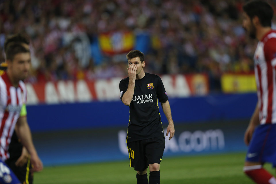 Photo - Barcelona's Lionel Messi covers his face during the Champions League quarterfinal second leg soccer match between Atletico Madrid and FC Barcelona at the Vicente Calderon stadium in Madrid, Spain, Wednesday, April 9, 2014. (AP Photo/Andres Kudacki)