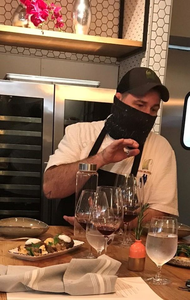Photo - Chef Josh Valentine, masked up, at Livegrass Butcher + Bistro.  [Dave Cathey/The Oklahoman]