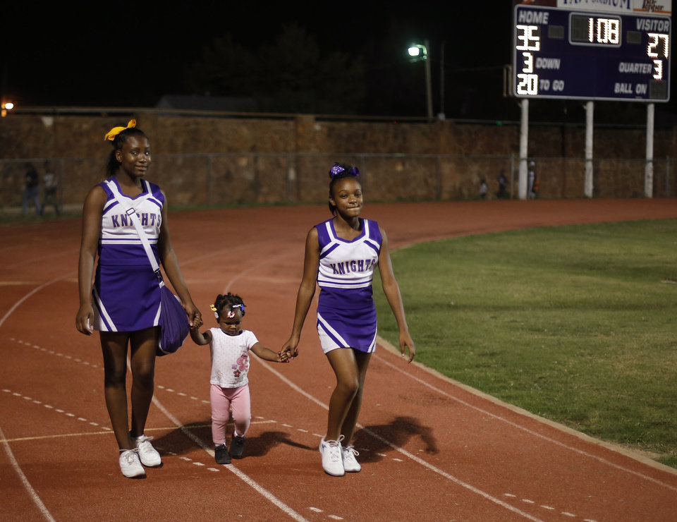 Two cheerleaders escort a young girl back from halftime at the Northwest Classen vs. Western Heights high school football game at Taft Stadium Thursday, September 20, 2012. Photo by Doug Hoke, The Oklahoman