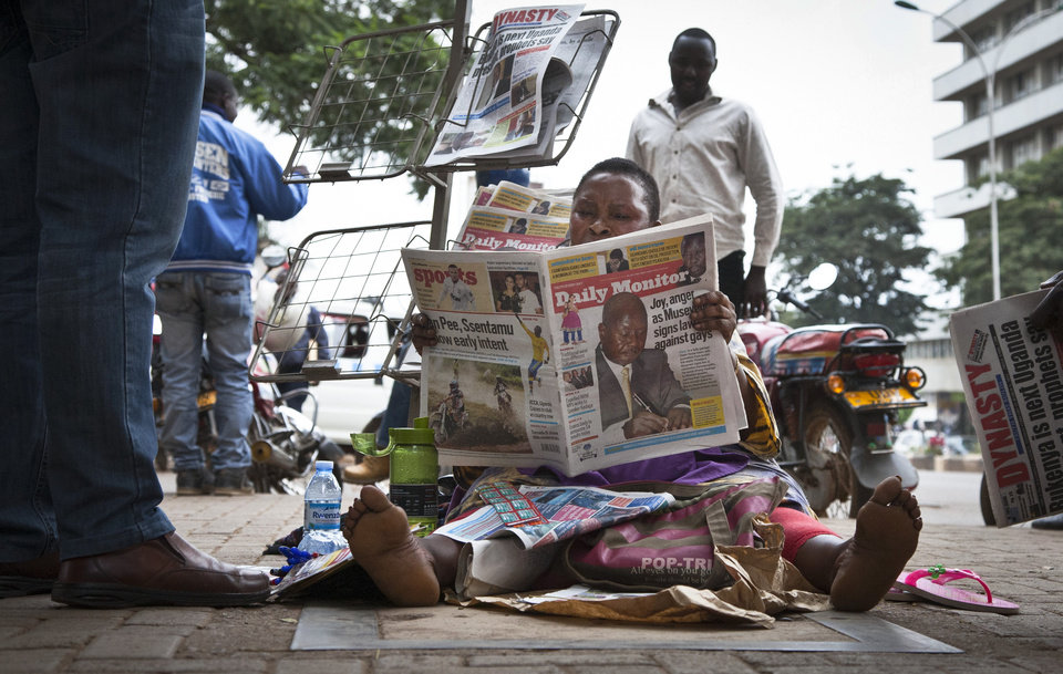 Photo - A Ugandan newspaper seller reads a copy of the
