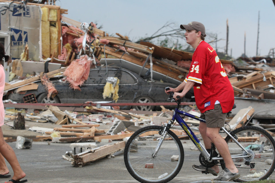 Photo - Onlookers make their way through the rubble left by a strong tornado Wednesday, April 27, 2011 Tuscaloosa, Ala. A wave of severe storms laced with tornadoes strafed the South on Wednesday, killing at least 16 people around the region and splintering buildings across swaths of an Alabama university town. (AP Photo/Caroline Summers)