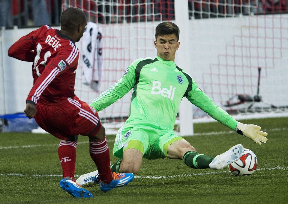 Photo - Toronto FC forward Jermain Defoe, left, score past Vancouver Whitecaps goal keeper Marco Carducci, right, during first half semi-final Amway Canadian Championship soccer action in Toronto on Wednesday, May 7, 2014. (AP Photo/The Canadian Press, Nathan Denette)