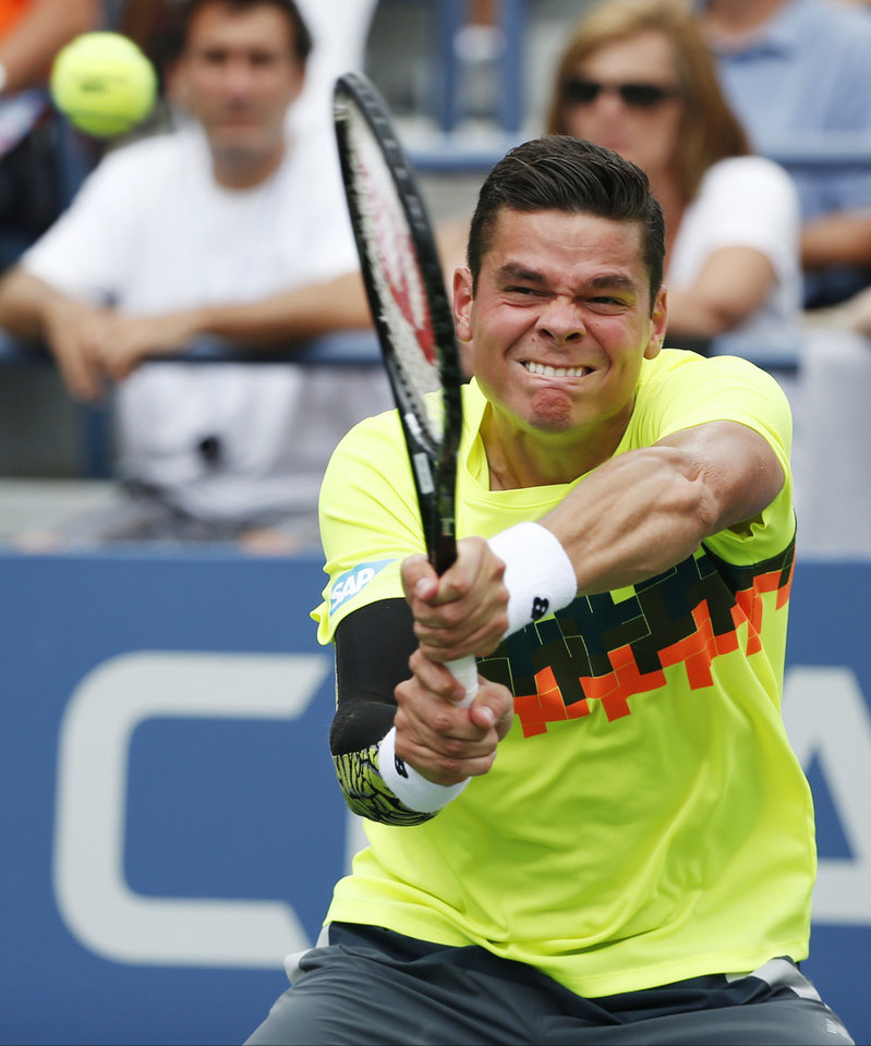 Photo - Milos Raonic, of Canada, returns a shot against Victor Estrella Burgos, of Dominican Republic, during the third round of the 2014 U.S. Open tennis tournament, Saturday, Aug. 30, 2014, in New York. (AP Photo/Kathy Willens)