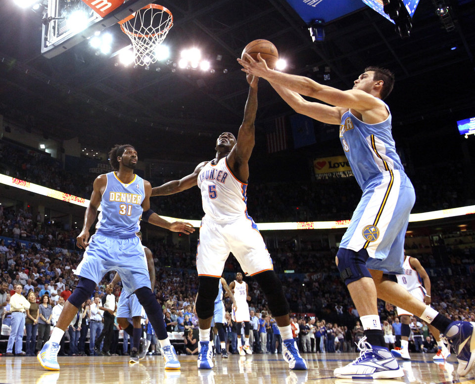 Photo - Oklahoma City's Kendrick Perkins (5) fights Denver's Nene (31) and Denver's Danilo Gallinari (8) from a loose ball during the NBA basketball game between the Oklahoma City Thunder and the Denver Nuggets, Friday, April 8, 2011, at the Oklahoma City Arena.. Photo by Sarah Phipps, The Oklahoman