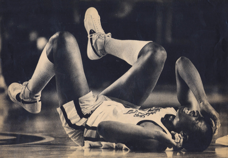 Photo - Tulsa Washington's Waymon Tisdale grimaces with pain after a second-quarter injury in the 1982 state tournament. Photo by Doug Hoke, The Oklahoman