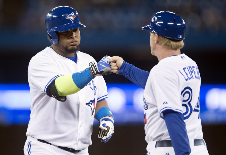 Photo - Toronto Blue Jays' Juan Francisco, left, celebrates a single with first base coach Tim Leiper during the third inning of a baseball game against the Philadelphia Phillies in Toronto on Thursday, May 8, 2014. (AP Photo/The Canadian Press, Darren Calabrese)
