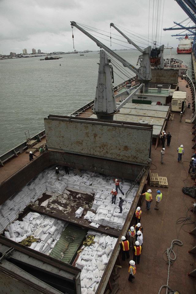 Photo - FILE - In this July 16, 2013 file photo, Panamanian workers stand atop sacks of sugar inside a container aboard a North Korean-flagged ship at the Manzanillo International container terminal on the coast of Colon City, Panama. Crews unloading the ship detained in the Panama Canal for carrying undeclared arms from Cuba have found live munitions aboard, a Panamanian official said Friday, Aug. 2, 2013. (AP Photo/Arnulfo Franco, File)