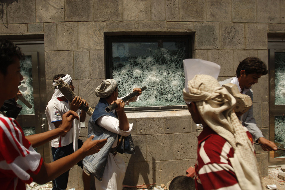 FILE - In this Thursday, Sept. 13, 2012 file photo, Yemeni protesters break a window of the U.S. Embassy during a protest about a film ridiculing Islam's Prophet Muhammad, in Sanaa, Yemen. A drive-by shooting that killed a top Yemeni security official who worked at the U.S. Embassy in Sanaa Thursday, Oct. 11, 2012 raises concern that al-Qaida militants here are bouncing back and getting bolder after suffering defeats this year in U.S.-Yemeni military offensive. Al-Qaida has carried out a string of assassinations of top government and military officials, reportedly has a hit list to kill more and has called for attacks on U.S. diplomatic missions.(AP Photo/Hani Mohammed, FIle)