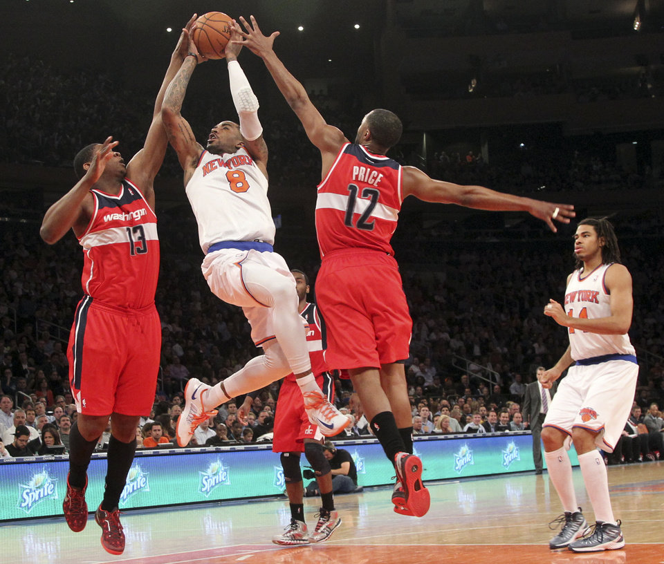 Photo - New York Knicks' J.R. Smith goes up past Washington Wizards' Kevin Seraphin (13) and A.J. Price during the second half of an NBA basketball game, Tuesday, April 9, 2013, at Madison Square Garden in New York. The Knicks won 120-99. (AP Photo/Mary Altaffer)