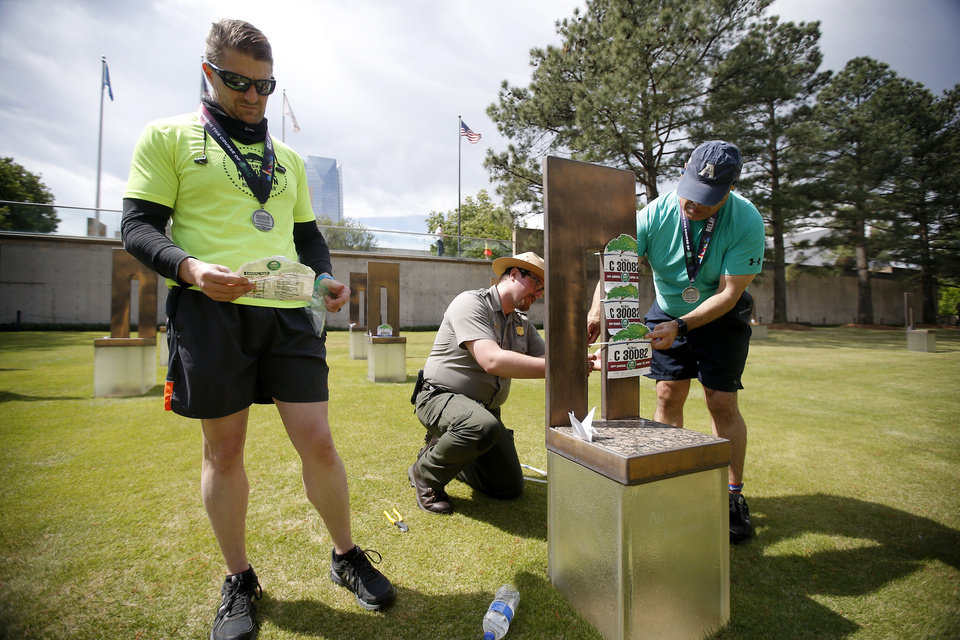 Photo - National Park Park Ranger Ian Harvey helps relay runners Steve Romero, right, and Damon Musick, left, place their bibs on the chair of Paul Gregory Beatty Broxterman after the two ran with the Ag Boyz relay team in the Oklahoma City Memorial Marathon in Oklahoma City, Sunday, April 28, 2019. [Bryan Terry/The Oklahoman]