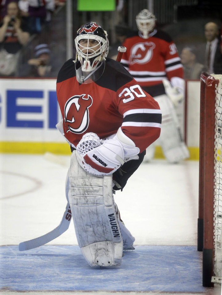 Photo - As fellow goalie Cory Schneider, background, looks on, New Jersey Devils goalie Martin Brodeur warms up in the goal before an NHL hockey game against the Boston Bruins in Newark, N.J., Sunday, April 13, 2014. (AP Photo/Mel Evans)