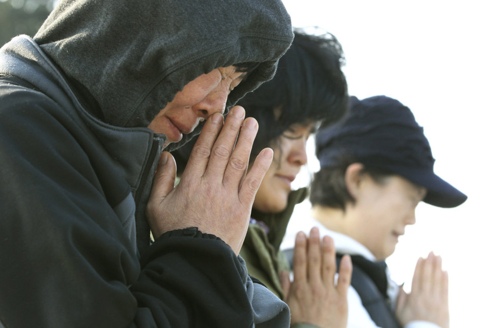 Photo - Relatives of passengers aboard the sunken ferry Sewol pray as they wait for their missing loved ones at a port in Jindo, South Korea, Monday, April 21, 2014. Divers continued the grim work of recovering bodies from inside the sunken South Korean ferry Monday, as a newly released transcript showed the ship was crippled by confusion and indecision well after it began listing. The transcript suggests that the chaos may have added to a death toll that could eventually exceed 300. (AP Photo/Ahn Young-joon)
