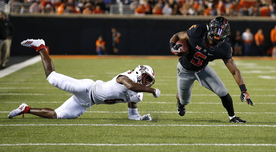 Photo - Oklahoma State's Justice Hill (5) gets by South Alabama's Nigel Lawrence (6) in the second quarter during a college football game between Oklahoma State (OSU) and South Alabama at Boone Pickens Stadium in Stillwater, Okla., Saturday, Sept. 8, 2018. Photo by Sarah Phipps, The Oklahoman