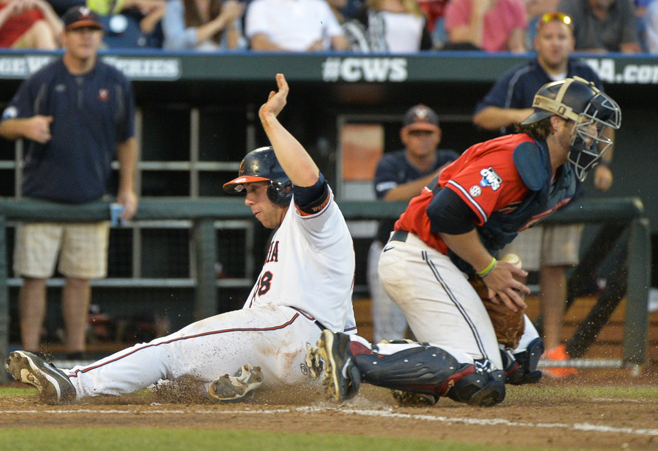 Photo - Virginia's Nate Irving, left, scores at home plate on a single by Joe McCarthy, before Mississippi catcher Will Allen controls the ball, in the fifth inning of an NCAA baseball College World Series game in Omaha, Neb., Sunday, June 15, 2014. (AP Photo/Ted Kirk)