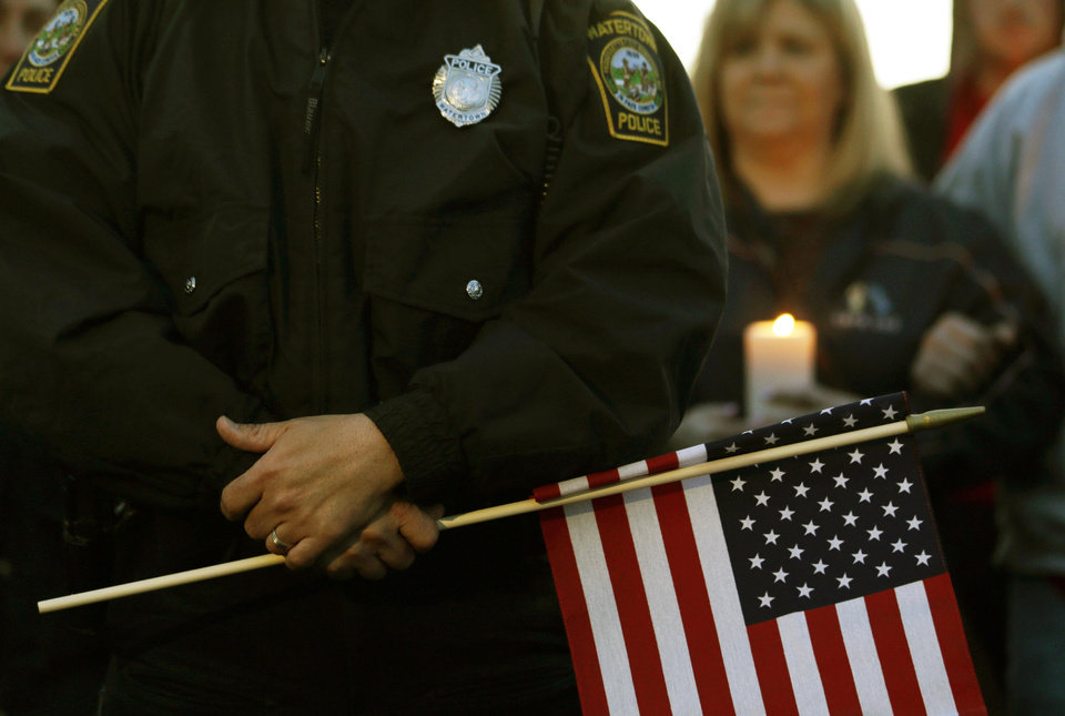 Watertown Police officer Brandon O\'Neill holds a flag during a vigil for the victims of the Boston Marathon bombing, Saturday, April 20, 2013, in Watertown, Mass. Suspected bomber Dzhokhar Tsarnaev is hospitalized in serious condition with unspecified injuries after he was captured in an all day manhunt the day before. (AP Photo/Julio Cortez) ORG XMIT: MAJC128