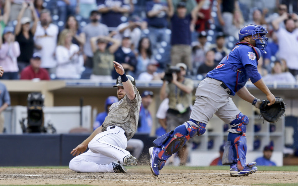 Photo - San Diego Padres' Logan Forsythe slides in safely with the game winning run as Chicago Cubs catcher Welington Castillo chases the late throw in the fifteenth inning of a baseball game won 3-2 by the Padres Sunday, Aug. 25, 2013, in San Diego. (AP Photo/Lenny Ignelzi)