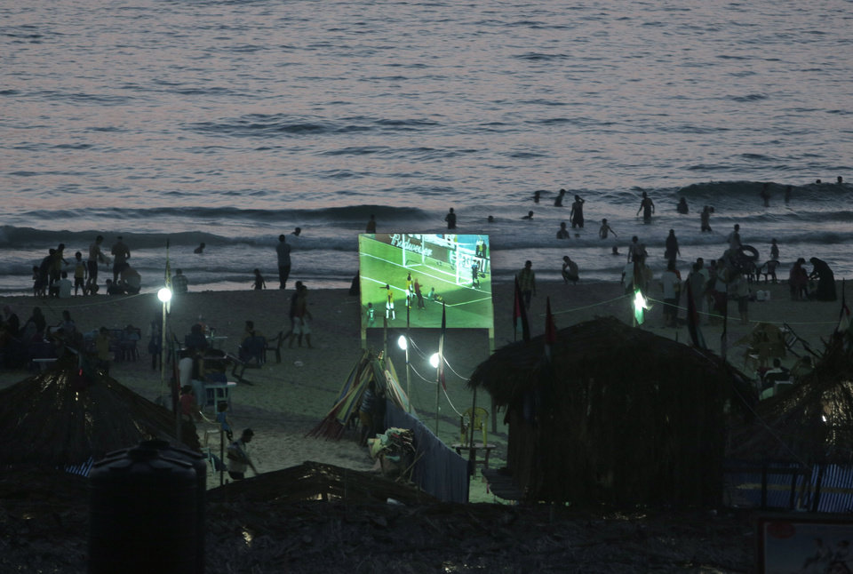Photo - FILE - In this Thirsday, June 19, 2014 file photo, Palestinians watch a World Cup football game on a wide screen on the beach of Gaza City. Politics and conflict are never far from soccer in the Middle East, but this year's World Cup has been entangled with unprecedented sectarian violence and soaring tensions between Arab countries, pushing fans to watch matches in secret or even on a channel owned by region's number one enemy _ Israel.(AP Photo/Khalil Hamra, File)
