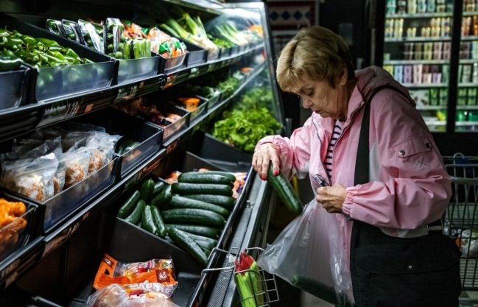 Photo -  Lavae Downey shops for vegetables at the Homeland grocery store in Yukon on Thursday. [Chris Landsberger/The Oklahoman]