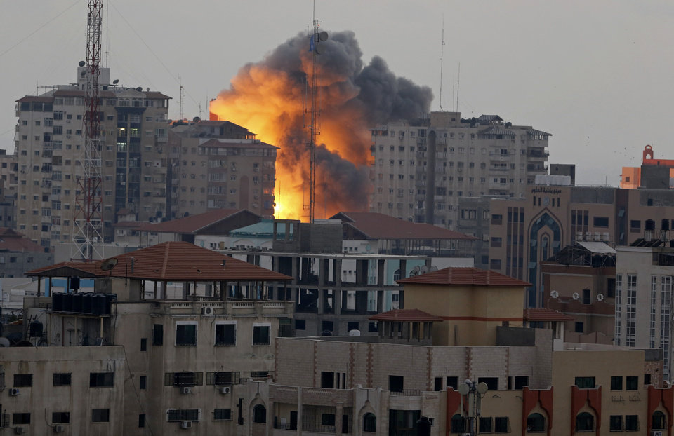 Photo - A ball of fire rises from an explosion on al-Zafer apartment tower following an Israeli air strike in Gaza City, in the northern Gaza Strip, Saturday, Aug. 23, 2014. Israeli aircraft fired two missiles at a 12-story apartment tower in downtown Gaza City on Saturday, collapsing the building, sending a huge fireball into the sky and wounding at least 22 people, including 11 children, witnesses and Palestinian officials said. (AP Photo/Adel Hana)