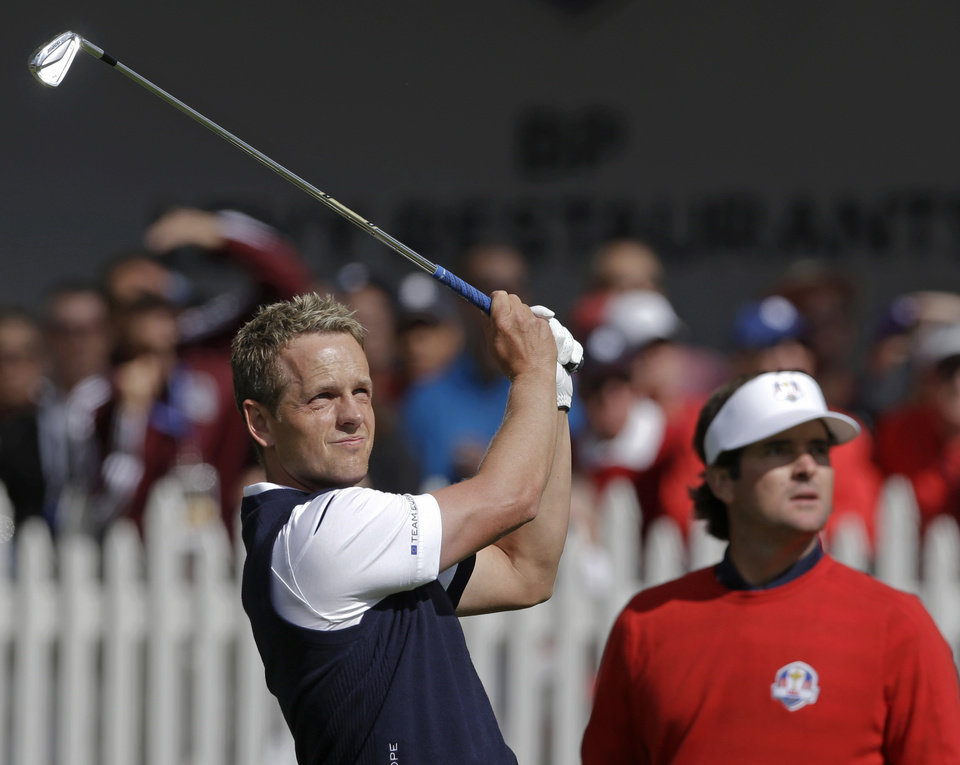 Photo - USA's Bubba Watson, right, watches as Europe's Luke Donald hits a shot during a singles match at the Ryder Cup PGA golf tournament Sunday, Sept. 30, 2012, at the Medinah Country Club in Medinah, Ill. (AP Photo/Chris Carlson)  ORG XMIT: PGA103
