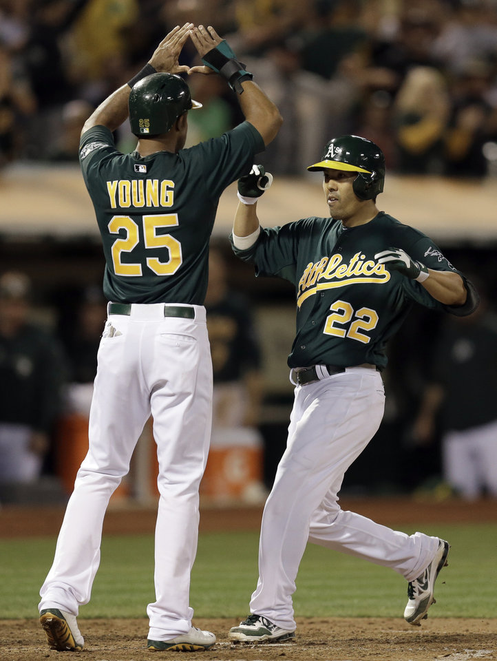Photo - Oakland Athletics' Kurt Suzuki (22) is congratulated by Chris Young (25) after Suzuki hit a three run home run off Tampa Bay Rays' David Price in the fifth inning of a baseball game Friday, Aug. 30, 2013, in Oakland, Calif. (AP Photo/Ben Margot)