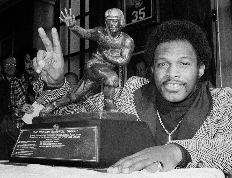 Photo - ** FILE ** Ohio State's running back Archie Griffin smiles as he poses with the 1975 Heisman Trophy, on Dec. 2, 1975, in New York City. Griffin who also won in 1974, is the first player to win the prestigious award twice. Griffin wouldn't mind sharing his claim to fame. The former Ohio State tailback is the only player to win two Heisman trophies, receiving his second in 1975. Oklahoma quarterback Jason White has a chance to match Griffin on Saturday when the Heisman is handed out in New York.  (AP Photo)