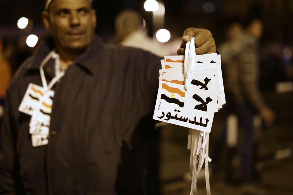 "An Egyptian vendor sells tags that read in Arabic, ""no to the constitution,"" outside the presidential palace, in Cairo, Egypt, Saturday, Dec. 8, 2012. Egypt's military warned on Saturday of ""disastrous consequences"" if the crisis that sent tens of thousands of protesters back into the streets is not resolved, signaling the army's return to an increasingly polarized and violent political scene.(AP Photo/Hassan Ammar)"