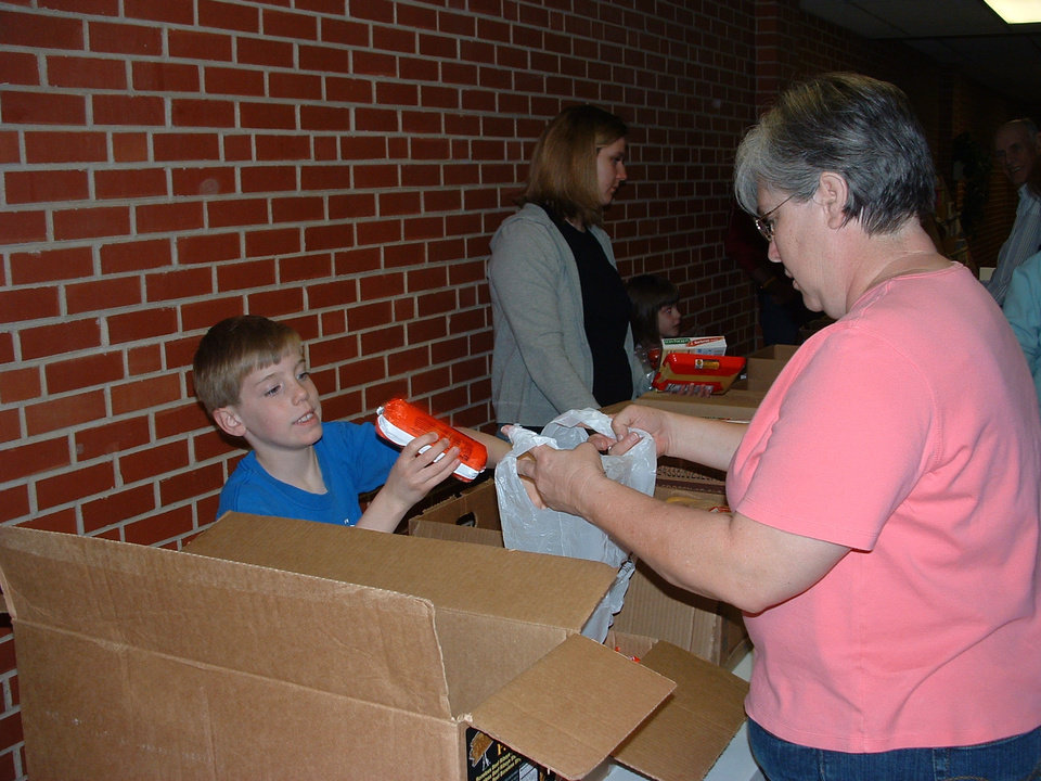 Heartland Share distribution day at Putnam City United Methodist Church. Volunteer Alex White helps fill a bag for participant Sienna Glass. See related story