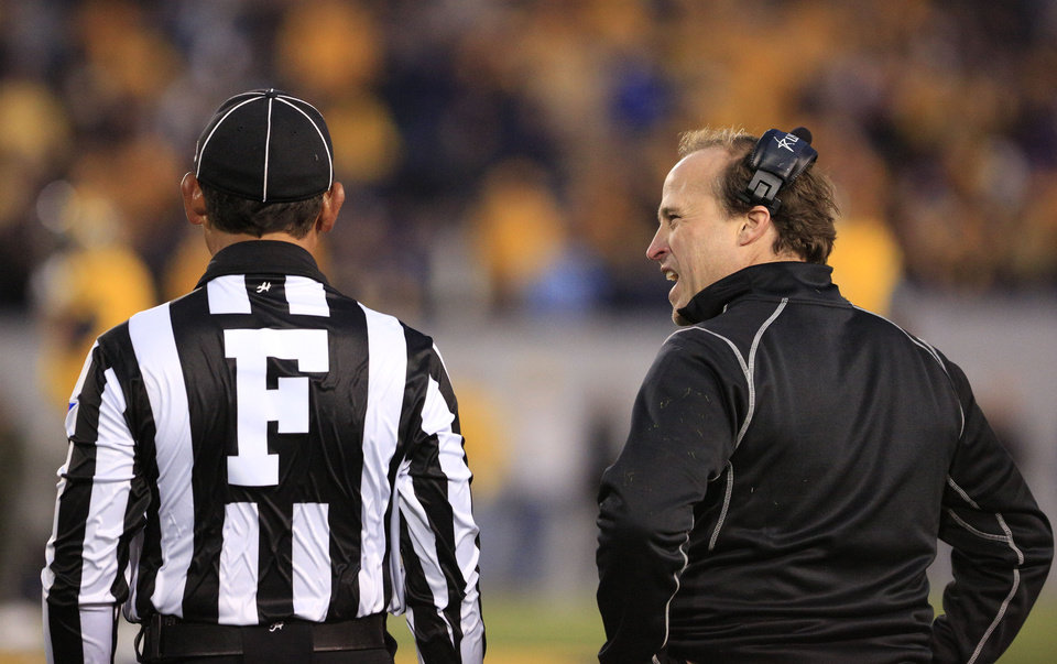 West Virginia coach Dana Holgorsen, right, talks with an official during their NCAA college football game against TCU in Morgantown, W.Va., on Saturday, Nov. 3, 2012. (AP Photo/Christopher Jackson) ORG XMIT: WVCJ127